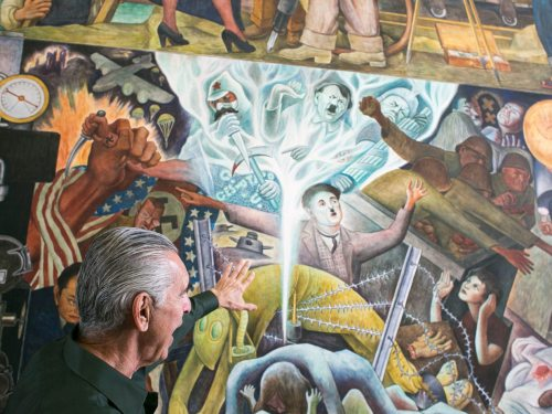 "Will Maynez, a retired physics lab manager caretaker of the ""Pan-American Unity"" mural, discusses the painting inside the Diego Rivera Theater at City College of San Francisco's Ocean View campus on April 4, 2017. (James Chan/Special to S.F. Examiner)"